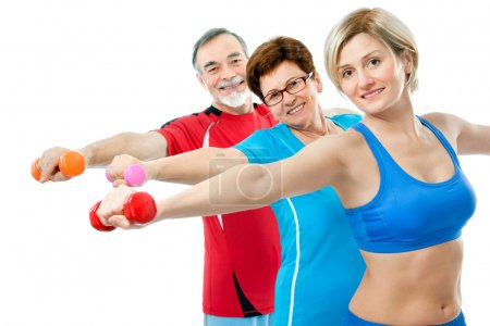 Photo for Seniors doing fitness exercises with help of trainer at sport gym - Royalty Free Image
