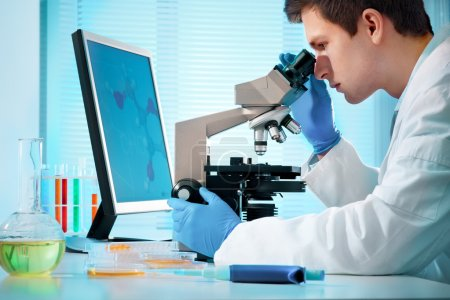 Scientist looking into microscope at the lab...