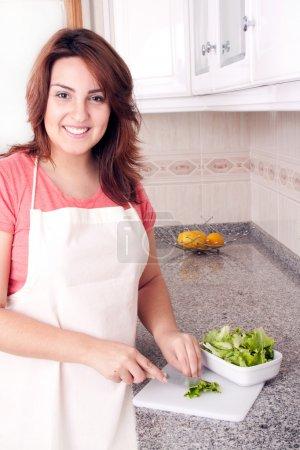 Photo pour Gros plan d'un légumes de coupe femme dans la cuisine pour sa salade - image libre de droit
