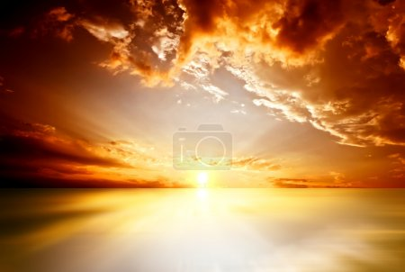 Photo for Red sunset over the sea, rich in dark clouds, rays of light - Royalty Free Image