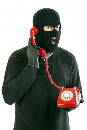Foto de Ladrón con máscara roja con una llamada telefónica - Imagen libre de derechos