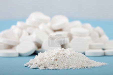 Photo pour Au premier plan des pilules écrasées sur un fond flou de comprimés entiers - image libre de droit
