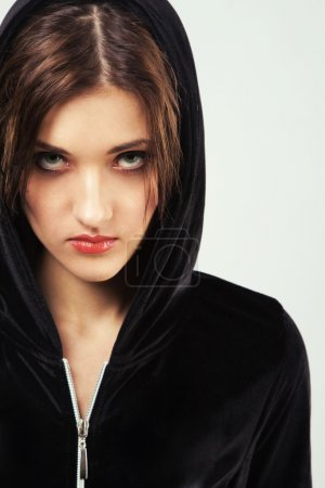 Portrait of a young angry woman in black hood...