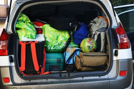 Very car with the trunk full of luggage ready for the departure of family h