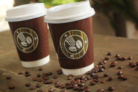 Photo pour Deux papier tasse de café pour aller sur une table à café en grains - image libre de droit