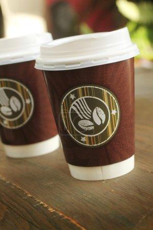 Photo pour Deux tasses de café pour aller sur une table en bois - image libre de droit