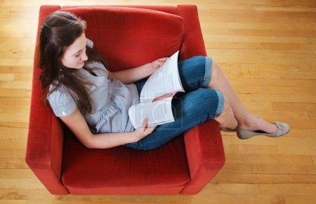 Photo pour Adolescent assis dans un canapé et lire un magazine - image libre de droit