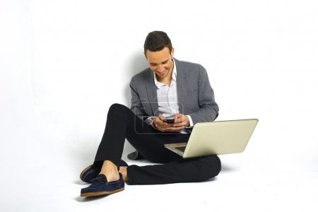 Smiling young business man with a laptop sitting at floor sending sms with a smartphone