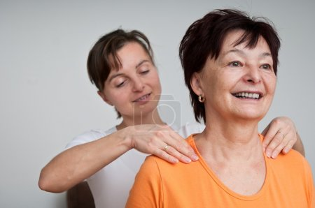 Photo for Senior woman receives neck massage from young person - Royalty Free Image
