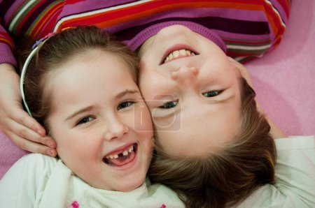 Smiling sisters lying in bed