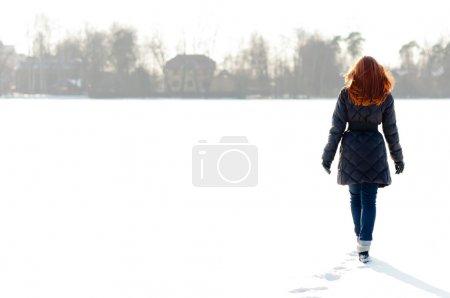 Photo pour Jolie fille aux cheveux rouges marchant sur le lac gelé et faisant sentier - image libre de droit
