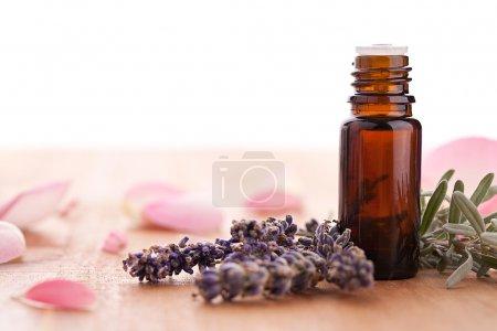 Photo pour Flacon de lavande et parfum avec des feuilles de rose sur fond bois. Pris dans Studio avec une marque 5D II . - image libre de droit
