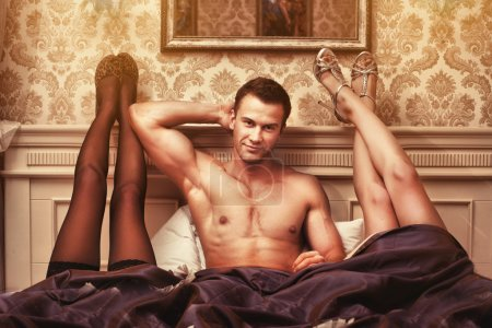 Photo for Handsome young muscular man with two women in bedroom - Royalty Free Image