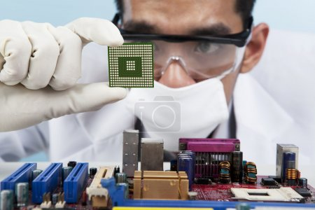 Photo for A scientist focusing at a chip of motherboard - Royalty Free Image