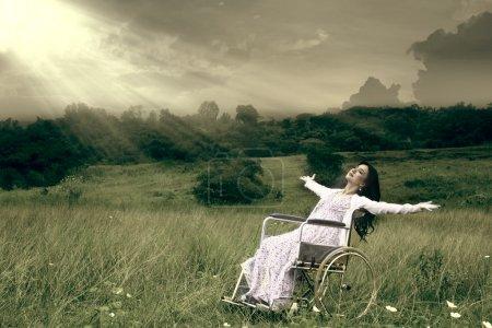 Photo pour Femme asiatique en fauteuil roulant embrassant la liberté en plein air - image libre de droit