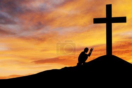 Photo pour Arrière-plan chrétien : Silhouette de l'homme priant sous la croix au coucher / lever du soleil - image libre de droit