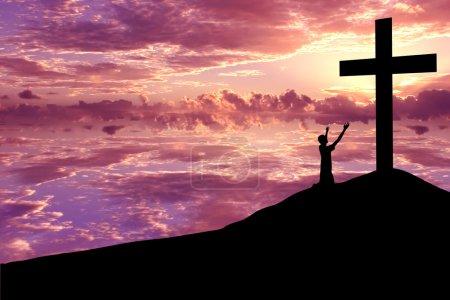Photo pour Christian Background : Silhouette de s l'homme wroship la croix au coucher du soleil ou au lever du soleil - image libre de droit