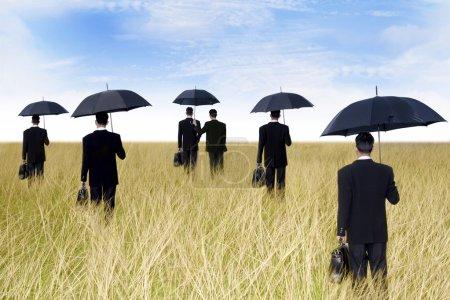 Photo pour Concept d'agent d'assurance : hommes d'affaires avec parapluie prêt à donner une protection - image libre de droit