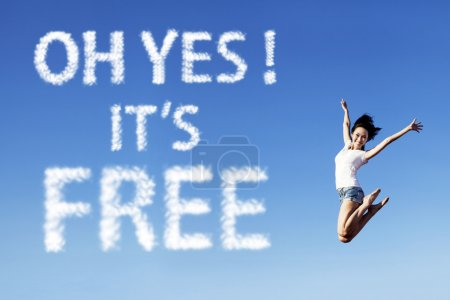 Photo for Happy woman jumping with a free writing cloud sign in the sky - Royalty Free Image