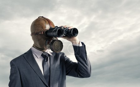 Photo for Businessman with gas mask looking through binoculars - Royalty Free Image