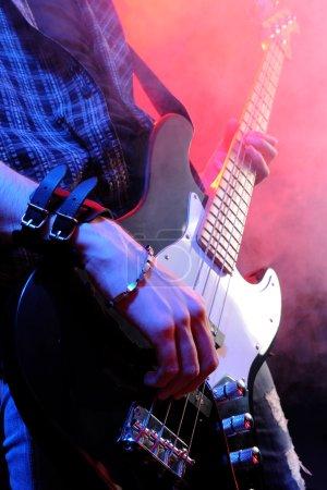 Close up of hands playing an bass