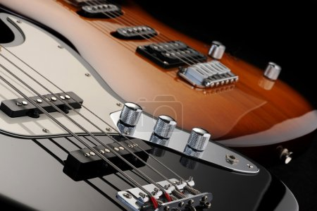 Photo for A close up of a electric guitar , and of a black bass glossy on dark background - Royalty Free Image