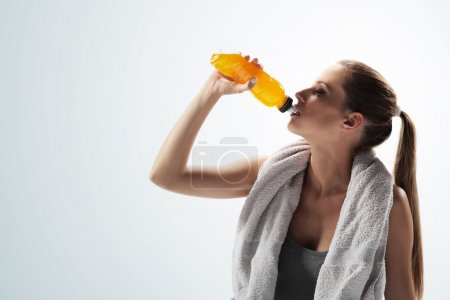 Photo for Thirsty young woman drinking after fitness workout - Royalty Free Image