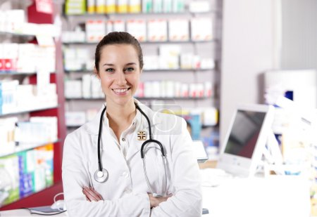 At pharmacy. A smiling young woman pharmacist with stethoscope