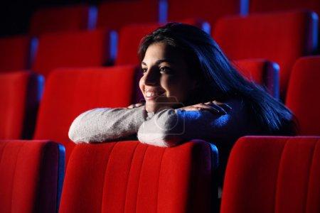 Photo pour Film drôle : portrait d'une jolie fille dans une salle de cinéma, elle s'appuie ses coudes sur la dernière rangée de chaises devant elle, en toute décontraction - image libre de droit