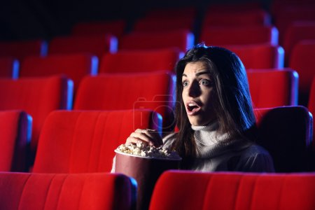 Photo for Scary movie: portrait of a pretty girl in an empty theater, she has expression of surprise and fear on his face - Royalty Free Image
