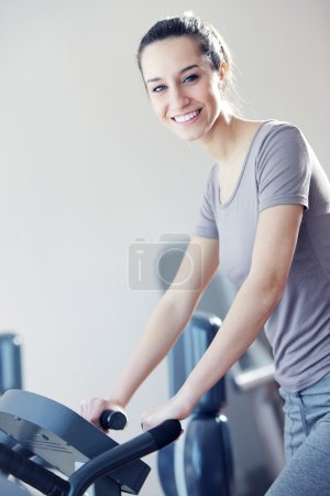 Portrait of young woman riding an exercise bike