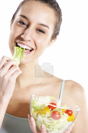 Photo for Woman eating salad. Portrait of beautiful smiling and happy woman enjoying a healthy salad and cherry tomatoes - Royalty Free Image