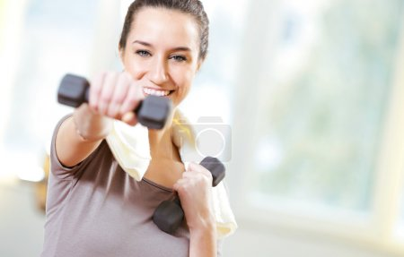 Photo for Dumbbell in hand of working out young smiling female - Royalty Free Image