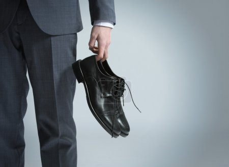 Photo for Businessman holding the shoes in hand, close up - Royalty Free Image