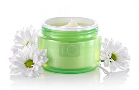 Foto de Envase de crema cosmética facial con margaritas blancas sobre un fondo blanco - Imagen libre de derechos