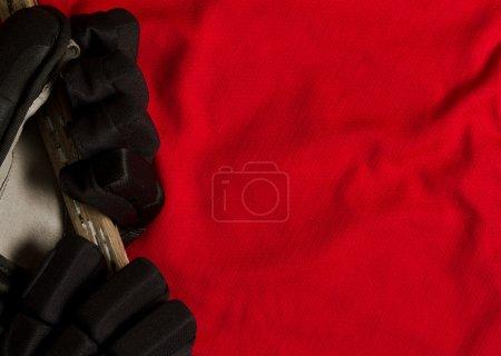 Photo pour Fond de hockey - gants sur maillot rouge avec espace de copie - image libre de droit