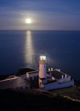 Lighthouse with Full Moon Reflecting in Sea