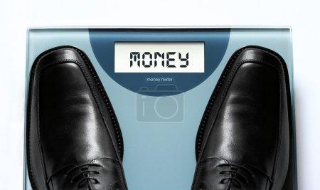 """Photo pour Concept de valeur et d'argent d'entreprise véhiculé par un homme d'affaires marchant sur une """"machine de pesage d'argent """" - image libre de droit"""