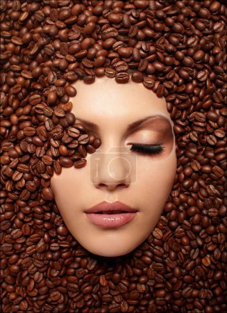 Portrait of a girl's face drowned in coffee beans bright brown makeup
