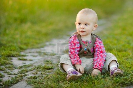 Foto de Retrato de una niña que se sienta en la hierba - Imagen libre de derechos