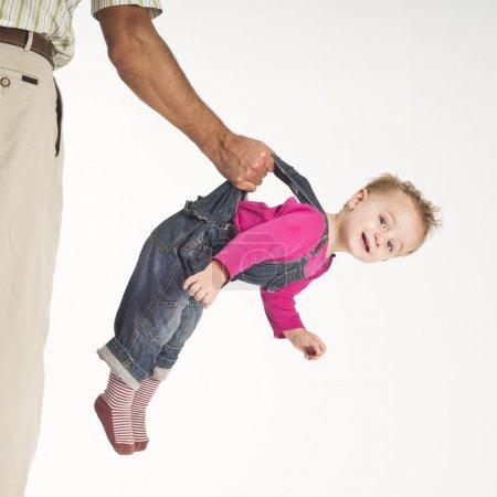 Photo pour Concept de soins, père tenant bébé bébé fille heureuse suspendue par des bretelles - image libre de droit