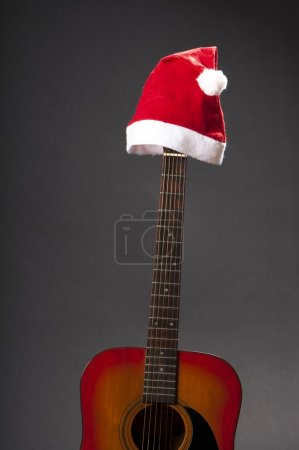 Classic accoustic guitar with santa claus' cap