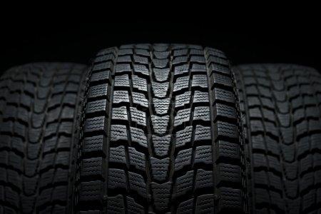 Three black winter tires in studio shot