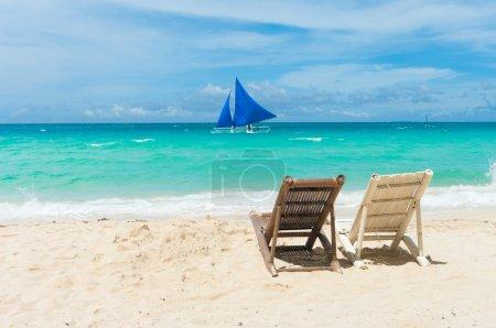Photo pour Plage tropicale avec deux chaises longues face à la mer bleue - image libre de droit