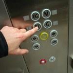 Man hand pushing B2 button in chrome elevator...