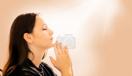 Photo pour Une femme priant avec des rayons de lumière descendant - image libre de droit