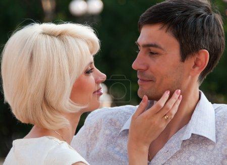 Beautiful couple, a woman stroking man's cheek. Love.