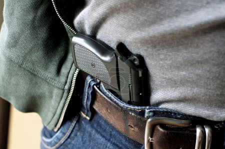 A tucked in a belt pistol is being concealed...
