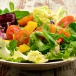 Lettuce salad with tomatoes and other vegetables served on a plate on wooden background