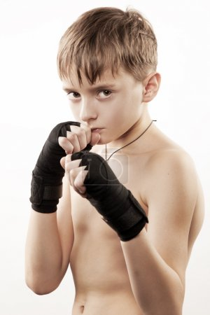 Young boy the boxer trains blow in strap
